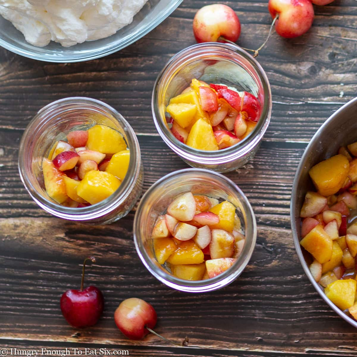Glass mason jars with fruit and shortcake inside.