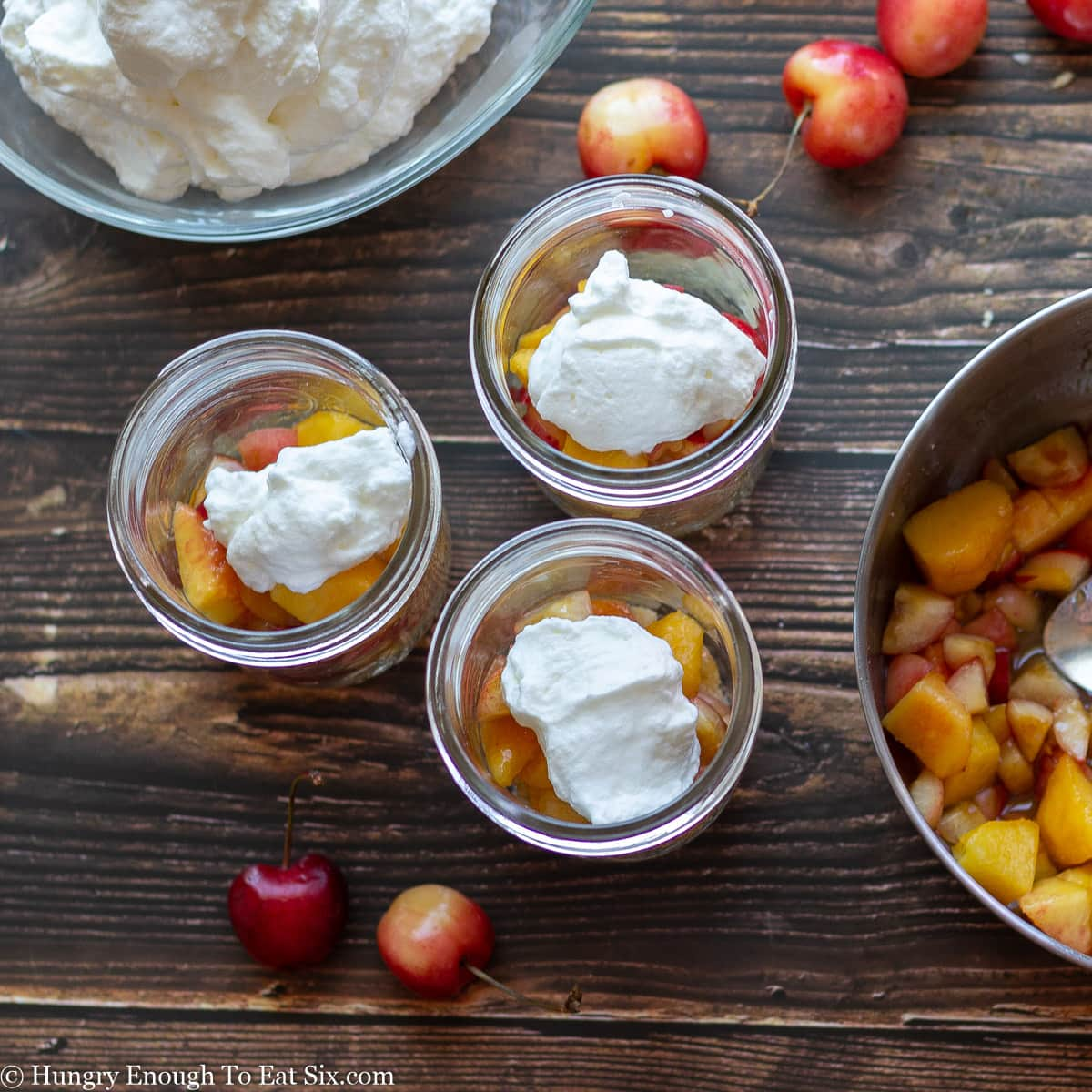 Mason jars with fruit and cream inside.