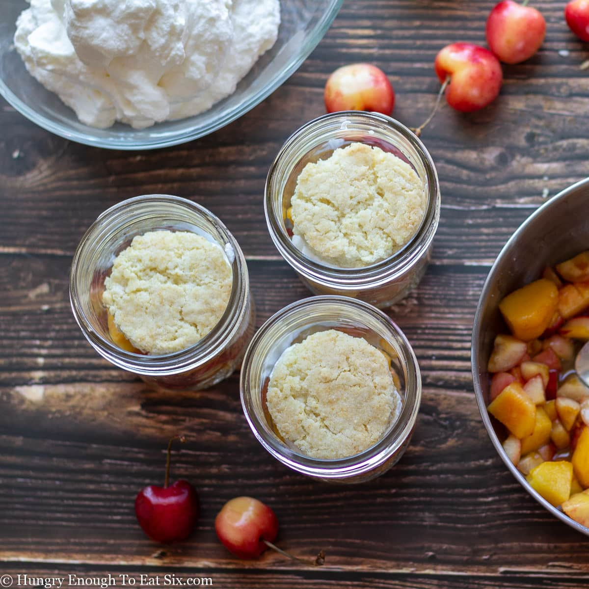 Glass mason jars with shortcake rounds next to bowls of fruit and cream.