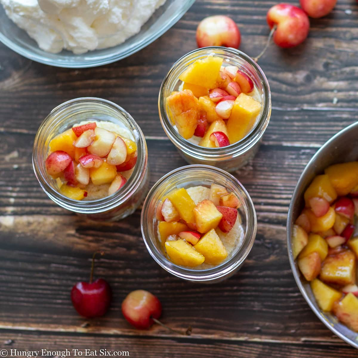 Glass jars holding diced nectarines and cherries with cherries on table.