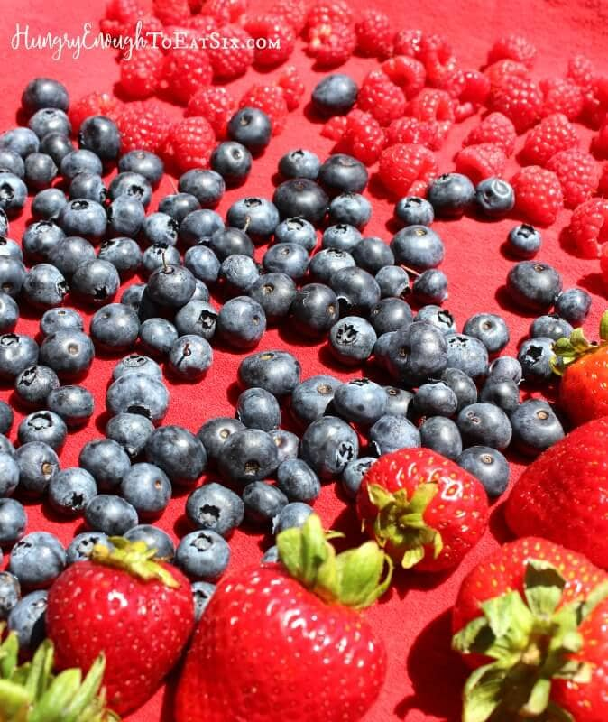 Blueberries, strawberries and raspberries on a red cloth.