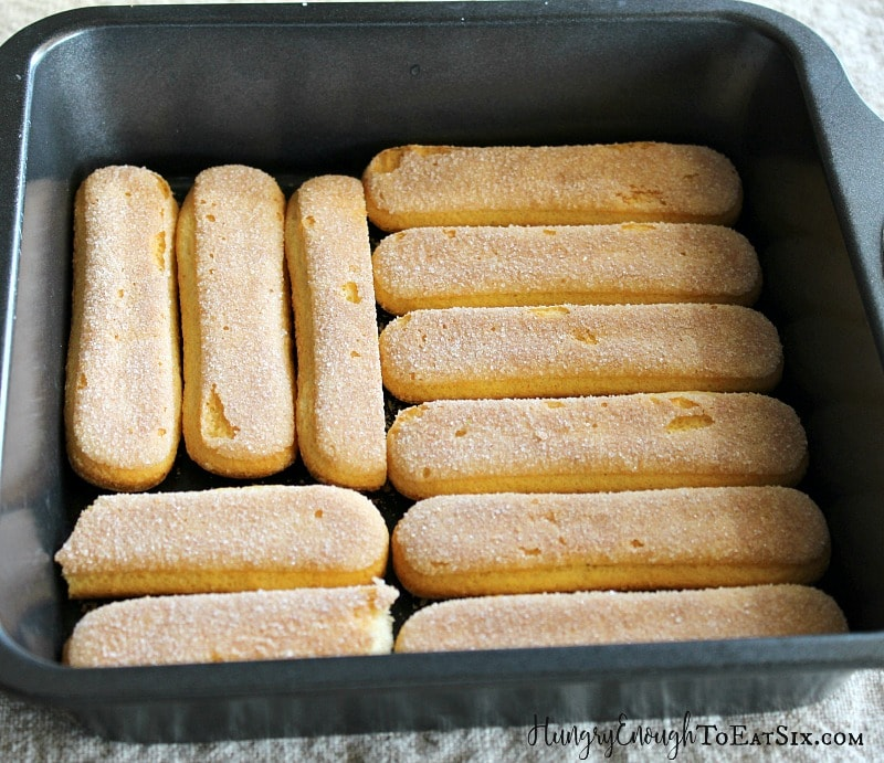 Ladyfinger cookies laid out in a square black pan.