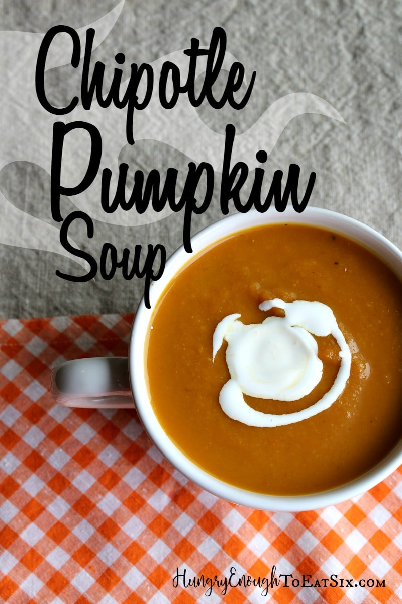 White large mug of pumpkin soup with text overlay.