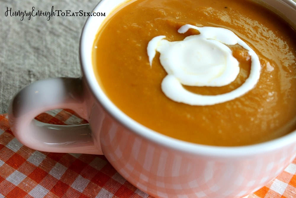 White mug with orange pumpkin soup.