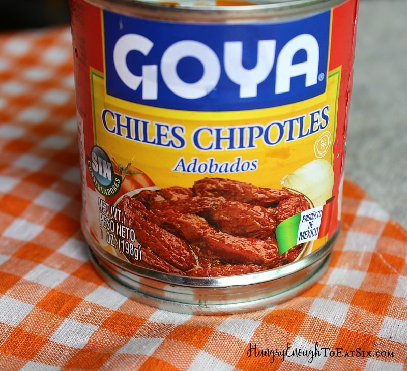 Small can of Goya chipotle peppers on an orange checked cloth.