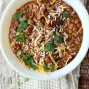 Vegetarian chili with cheese and chopped cilantro in a white bowl