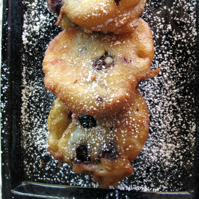 Image of blueberry fritters on a dark blue pallter