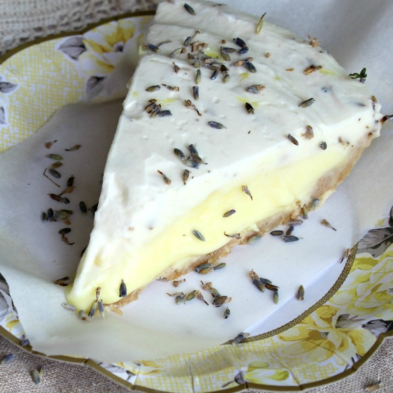 Slice of cold lemon pudding pie with a whipped cream top layer and lavender.