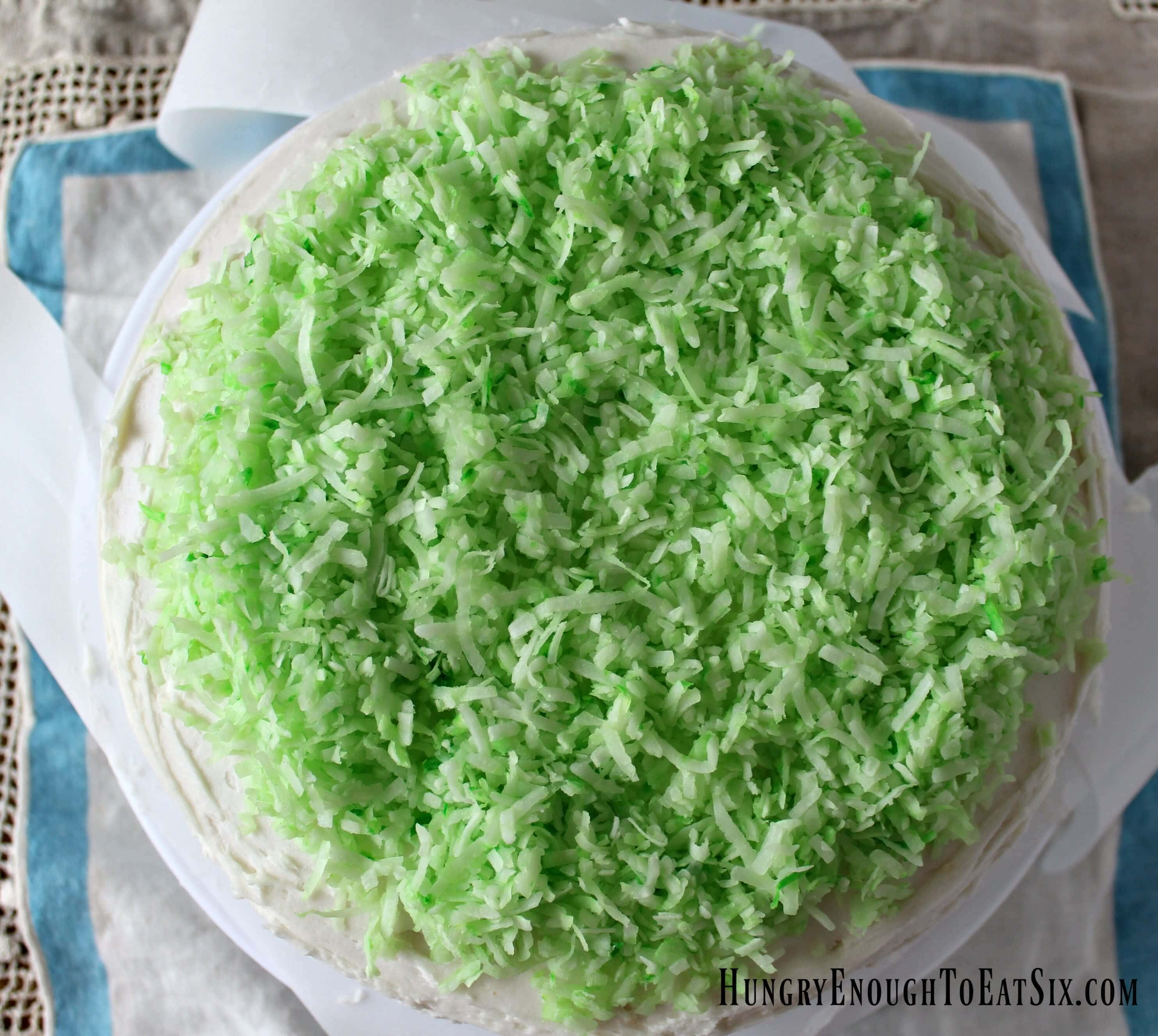 Think Spring and eat it too! This cake is full of bright lemon flavor, buttercream, and happy spring chicks on coconut grass,