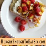 Grilled Peaches+Cream Shortcake With A Few Red Raspberries! A tender shortcake holds creamy mascarpone whipped cream and swirls of honey. Grilled peaches are piled on with a few red raspberries. It's a decadent and eye-catching dessert!