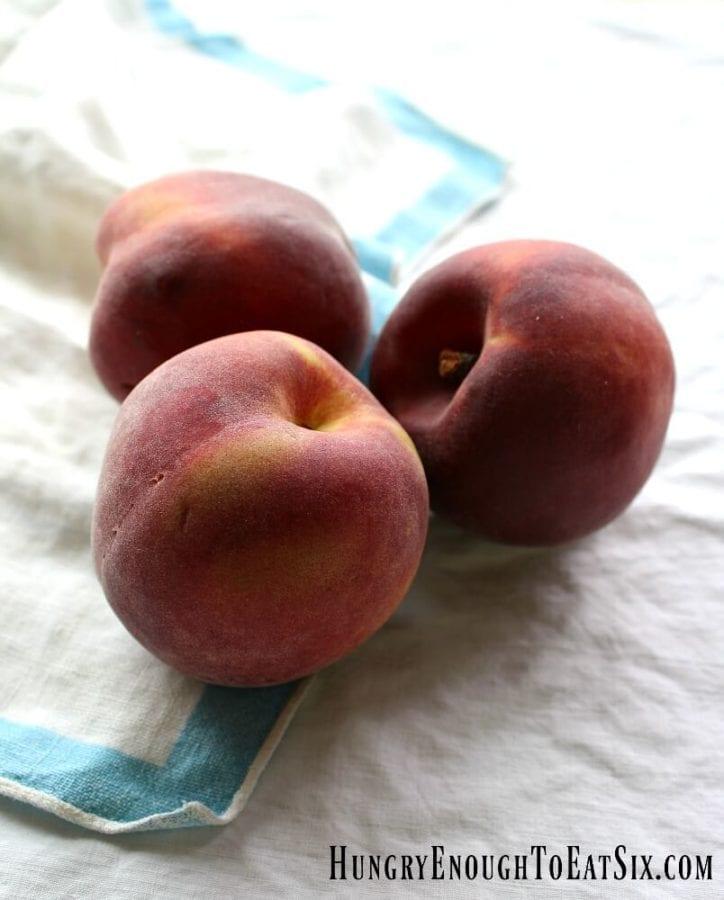 Three peaches on white and blue cloths