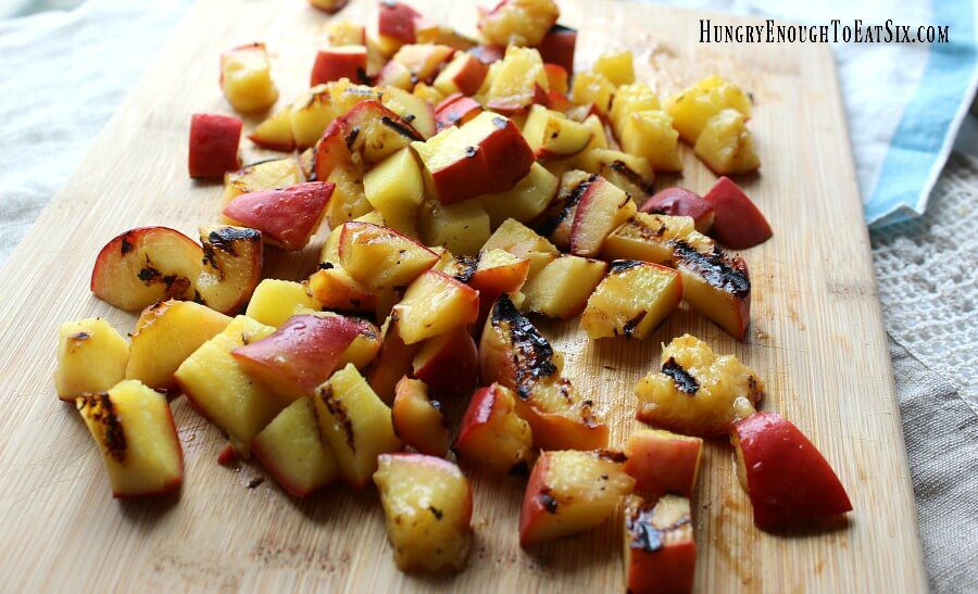 Cut pieces of grilled peaches on a cutting board
