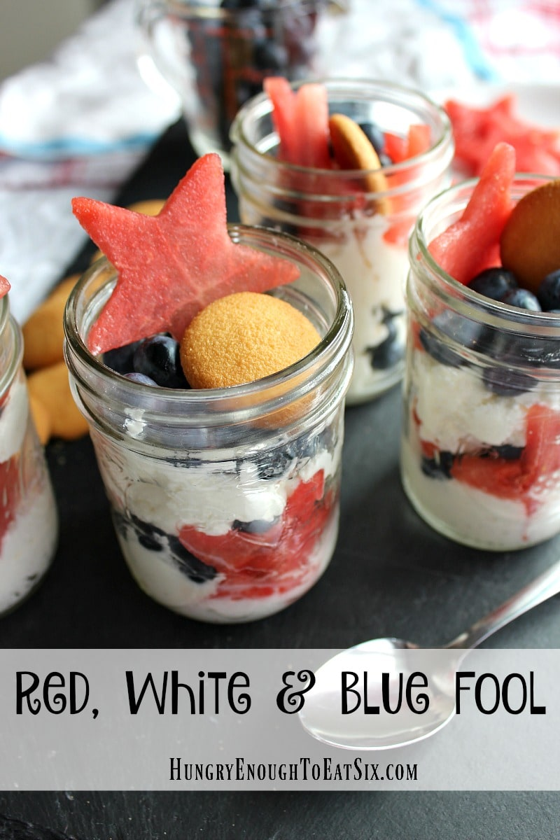Watermelon, Blueberries & Cream layered dessert in clear mason jars, with a cookie and watermelon star on top.
