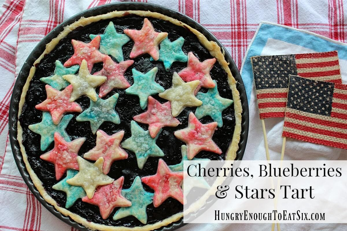 A finished round tart with cherry-blueberry filling and red, white and blue stars over the top.