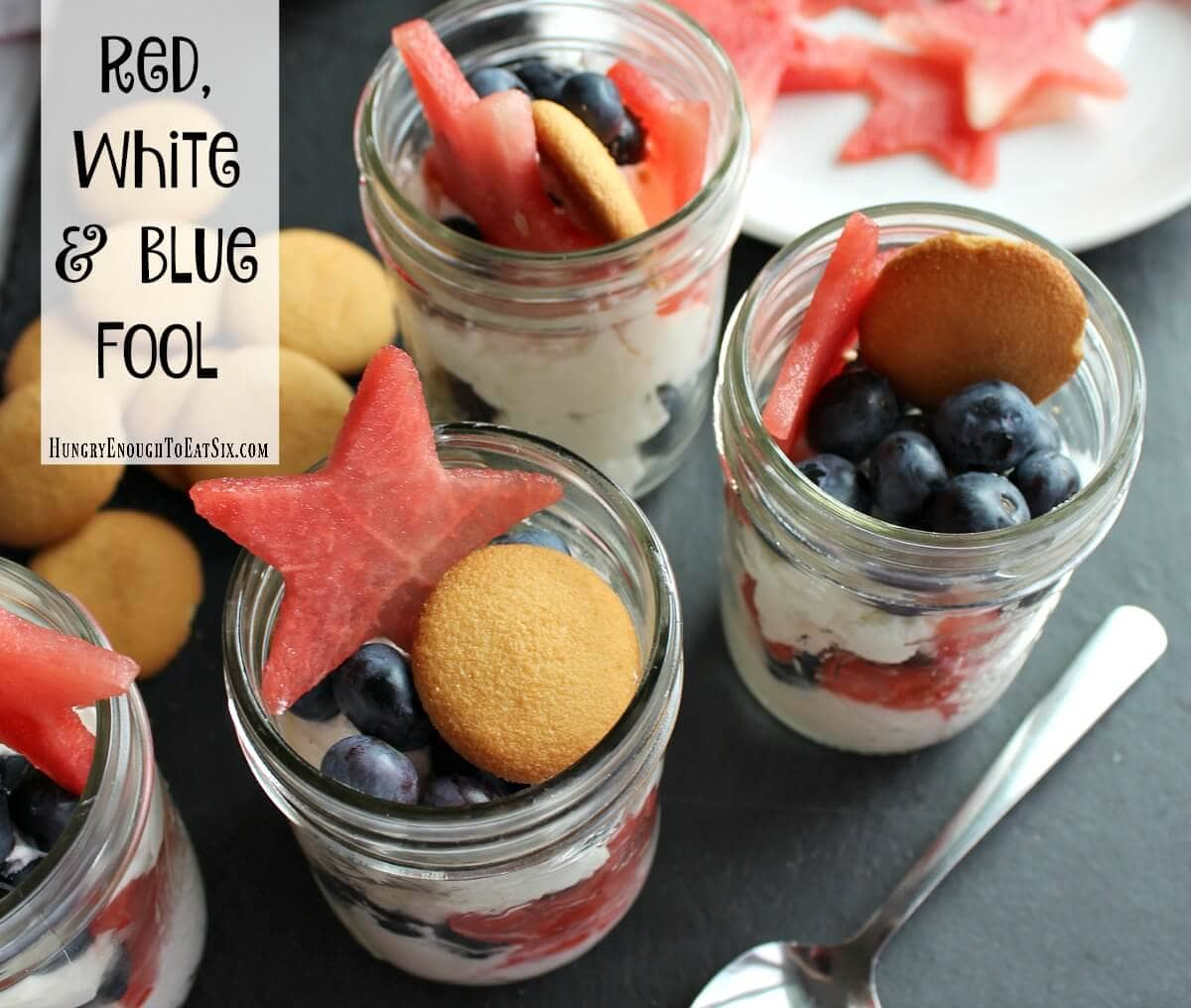 Small mason jars holding blueberries, watermelon stars and whipped cream.