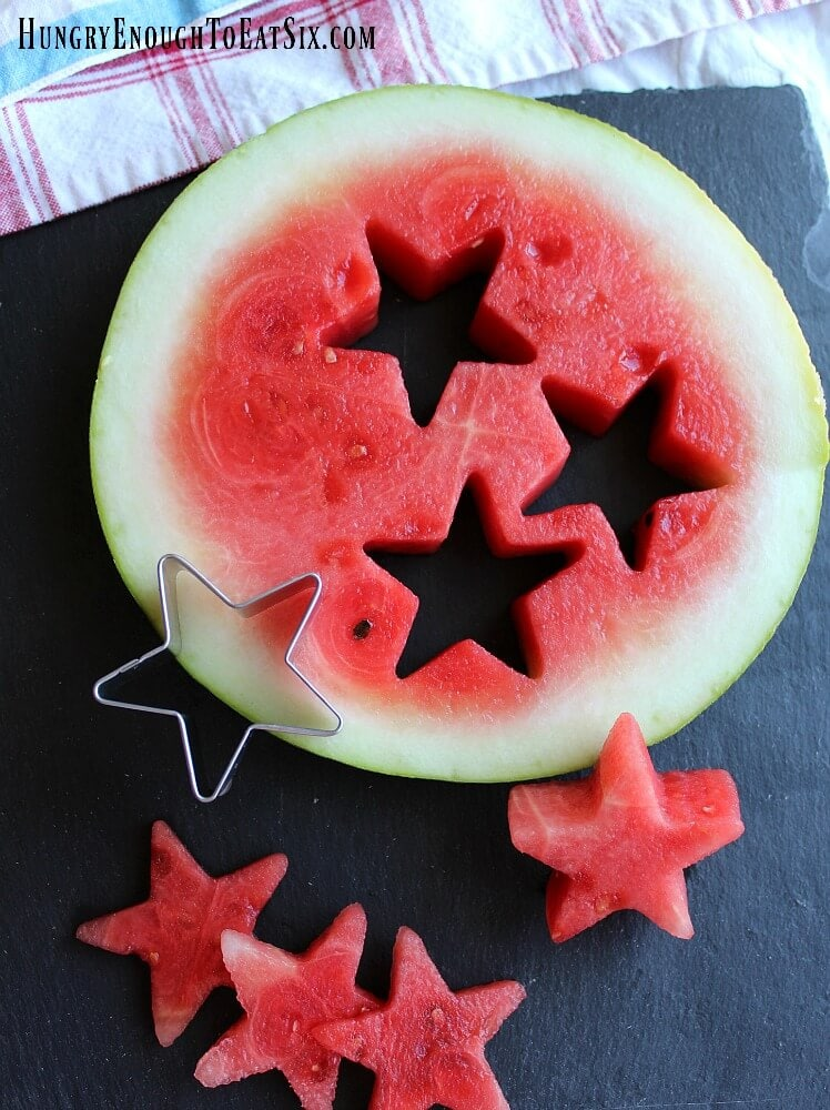 A round slice of watermelon with stars cut out on a black slate board.