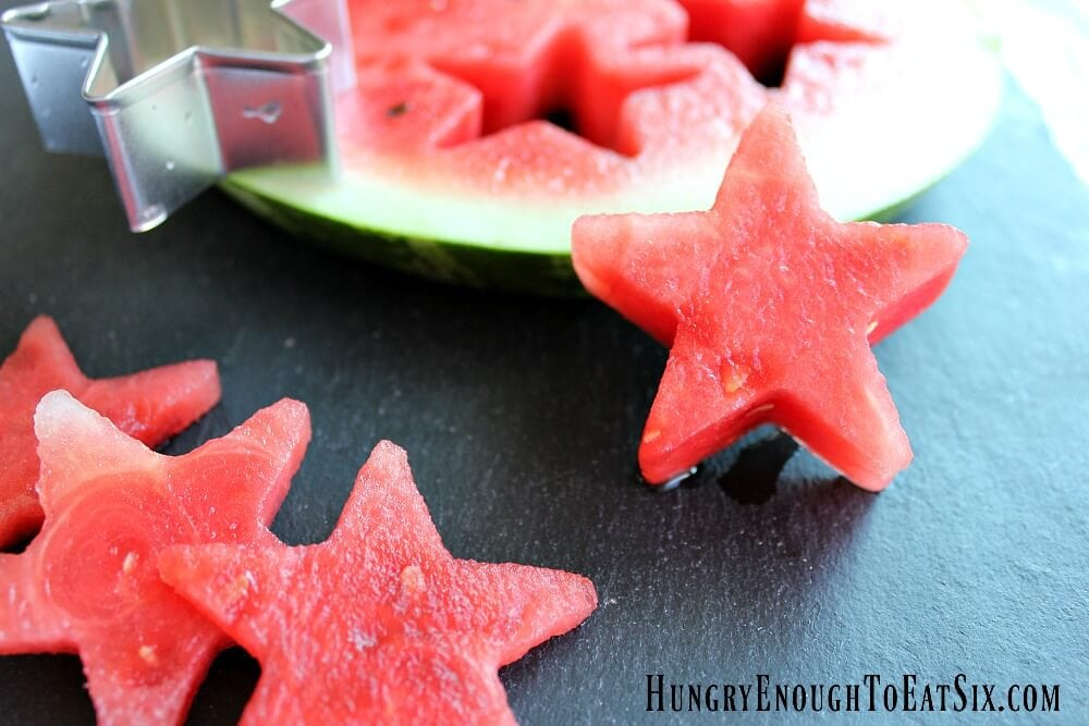 Stars cut out of watermelon slice on a black slate board.
