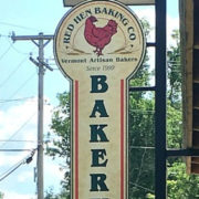 Red Hen Baking Company sign hanging outside on building.