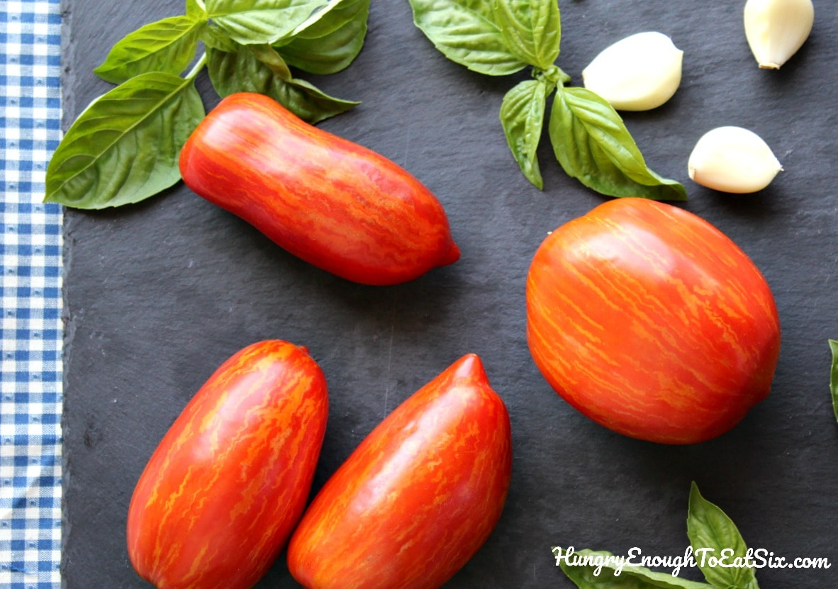 Roma tomatoes on a black slate board