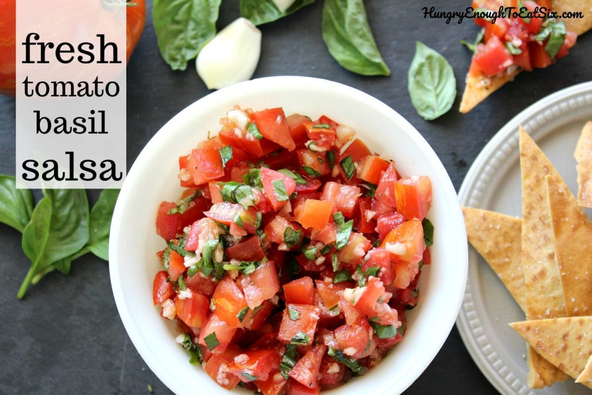 Fresh salsa with tomato, garlic and basil leaves in a white round bowl