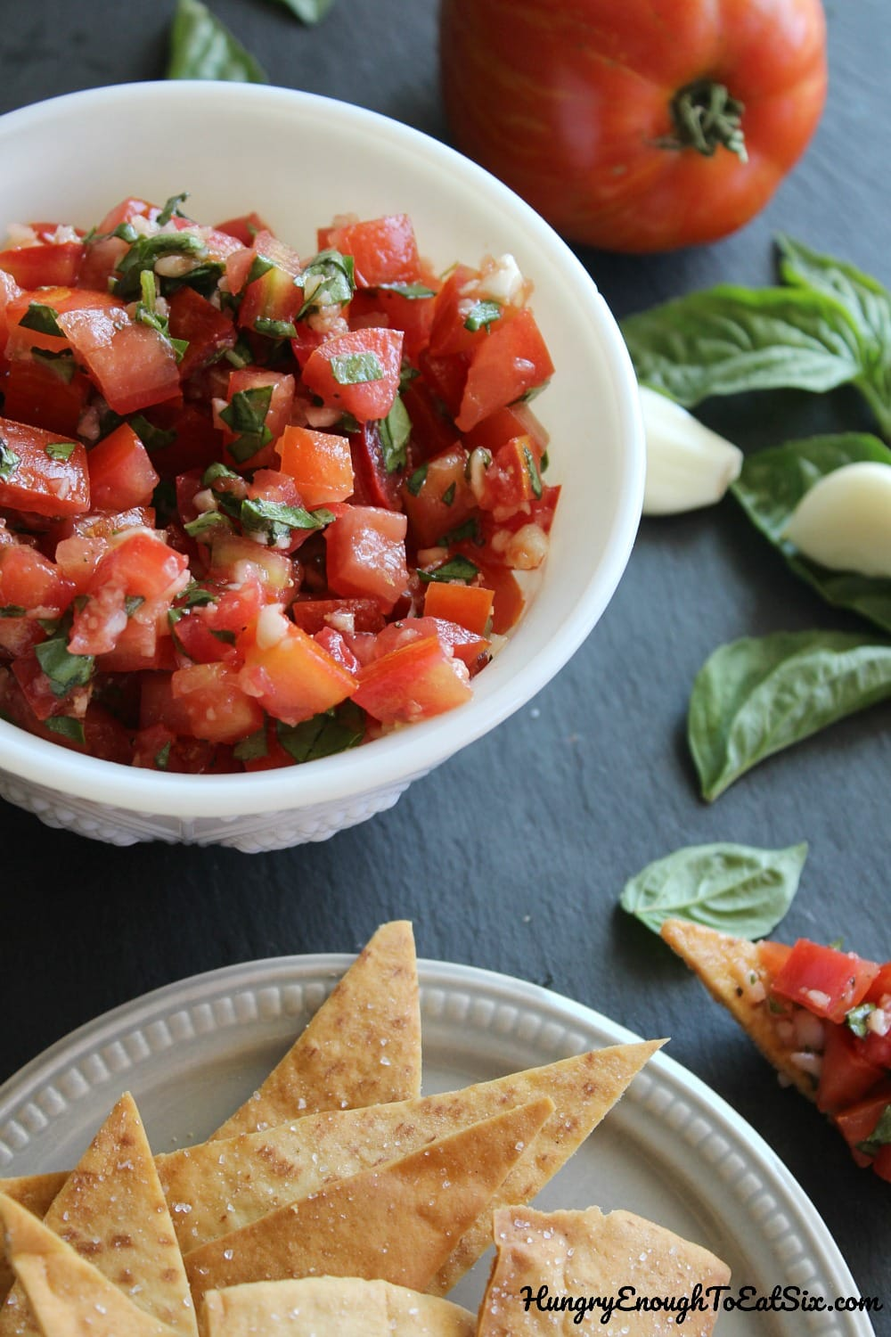 Plate of pita chips next to a bowl of tomato salsa