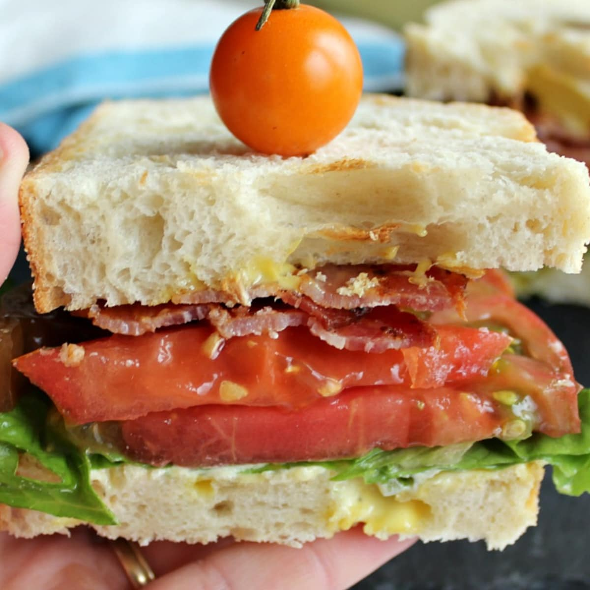 White bread sandwich with tomato and lettuce in a hand