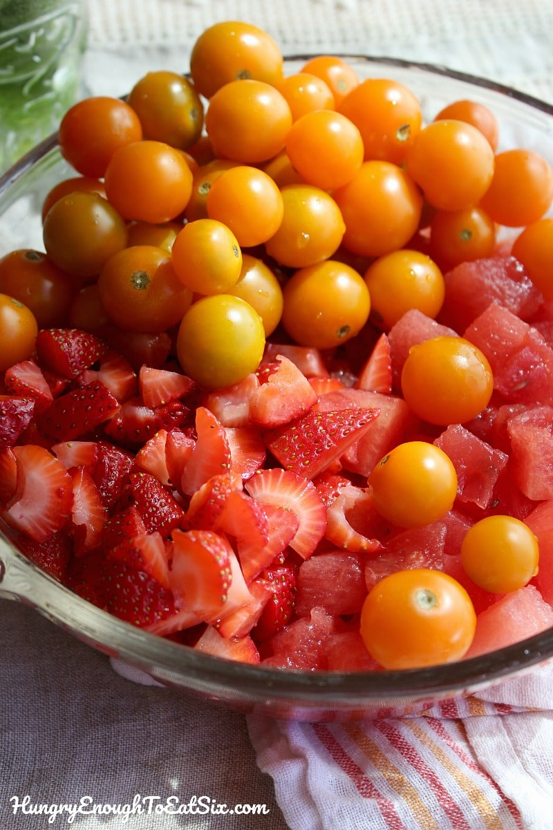 Large bowl with chopped strawberries, watermelon and cherry tomatoes