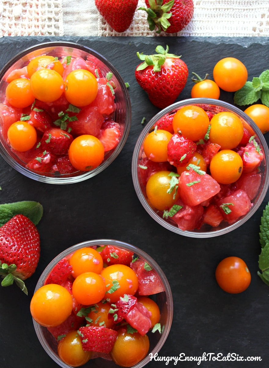 Three bowls of fruit salad with yellow cherry tomatoes