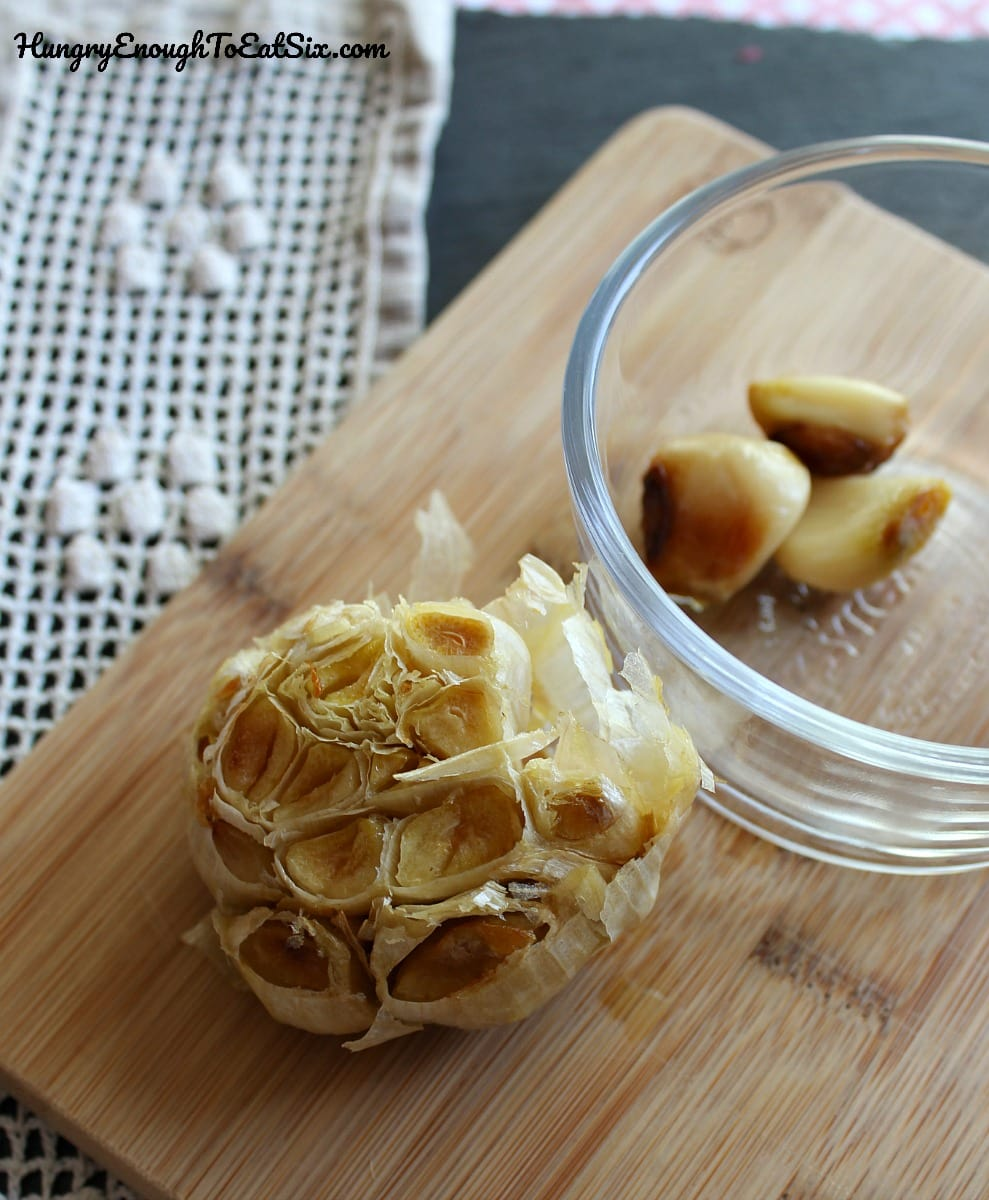 Roasted head of garlic on a wooden cutting board.