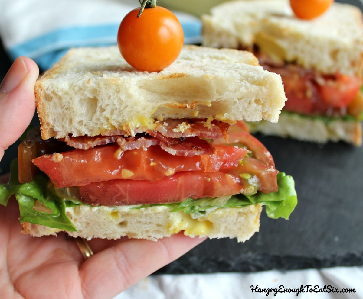 Hand holding half a sandwich with a tomato on top
