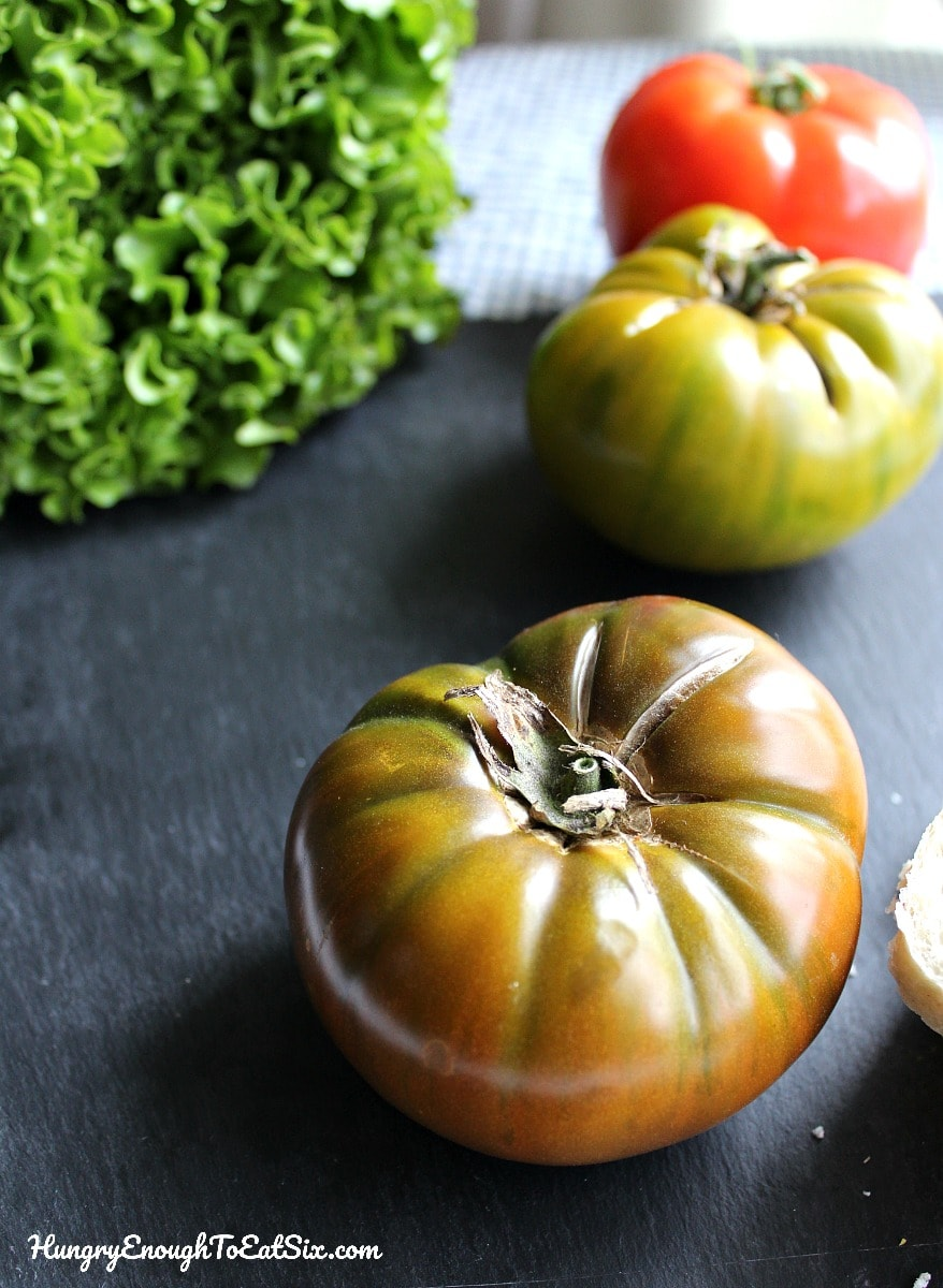 Whole heirloom tomatoes on a black board