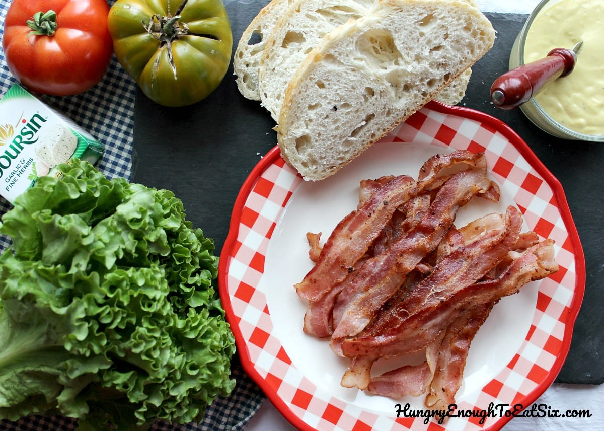 Plate of cooked bacon with lettuce, bread, and tomatoes nearby
