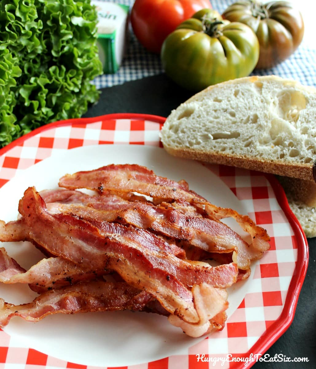 White and red plate with cooked bacon and a slice of bread