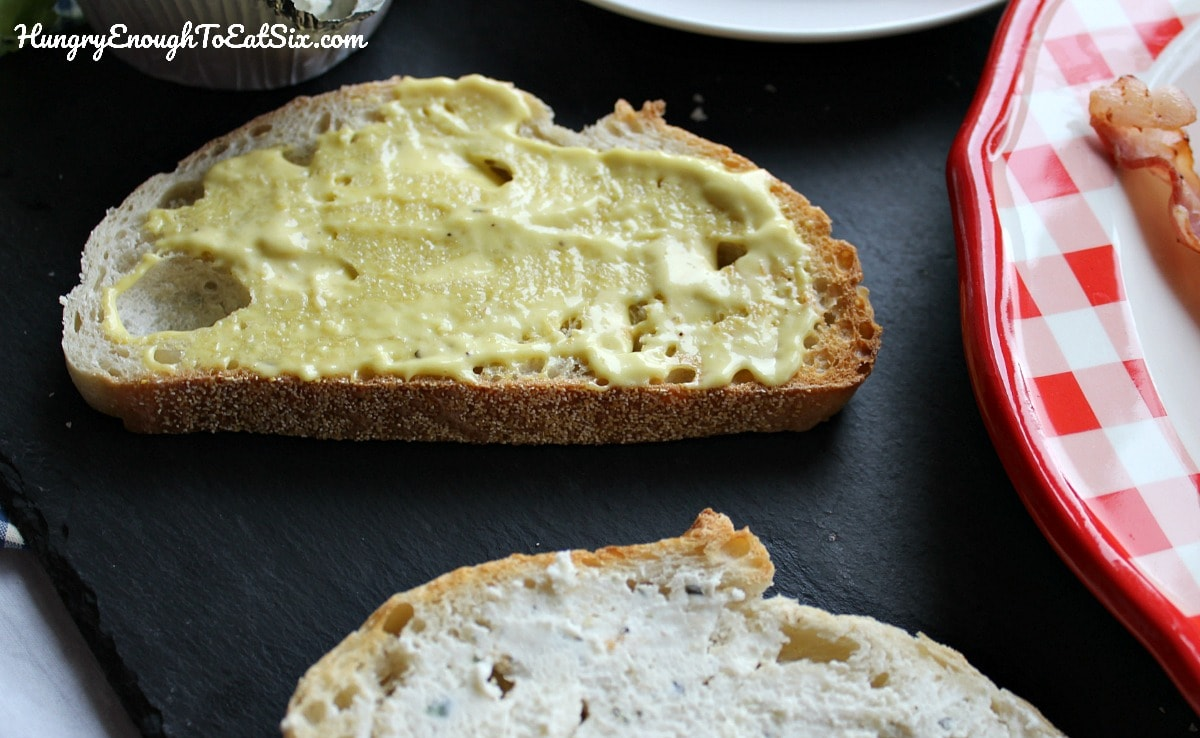 Slice of bread spread with yellow mayonnaise