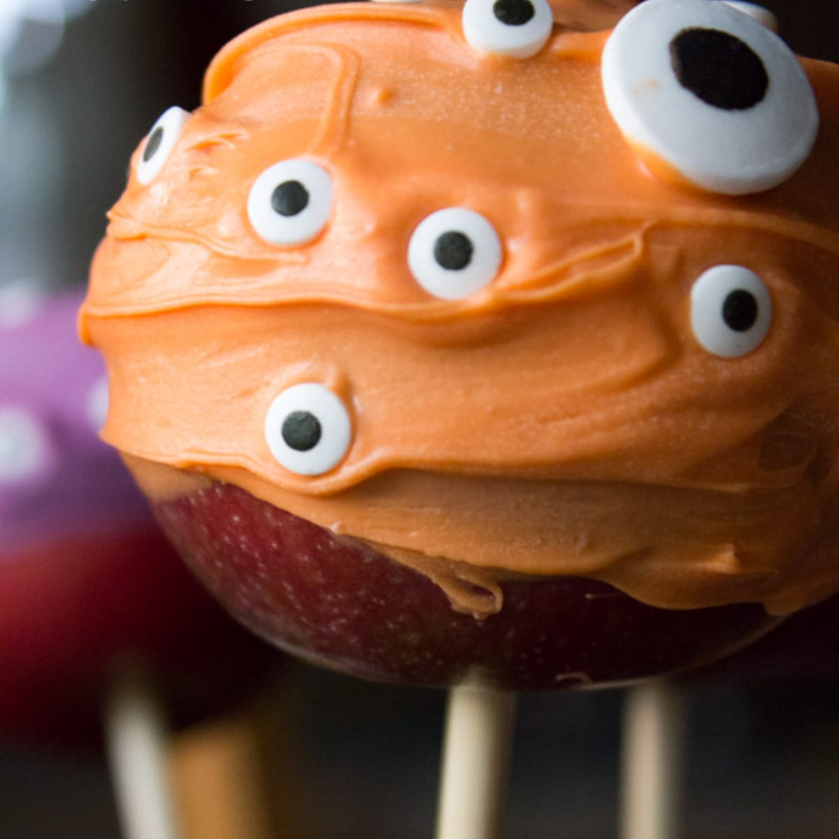 Orange coated apple with candy eyes, on a wood stick
