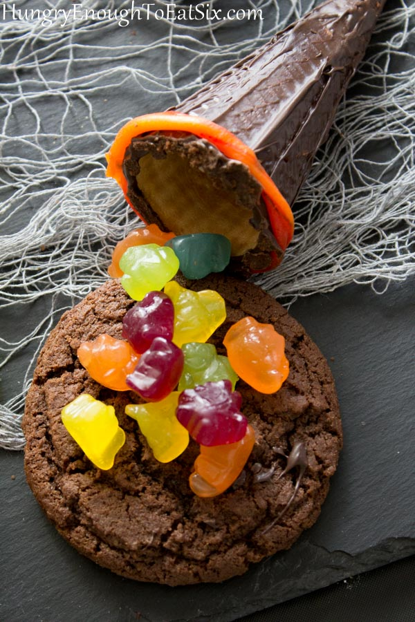 Pile of gummy candies on a chocolate cookie with a chocolate covered cone.