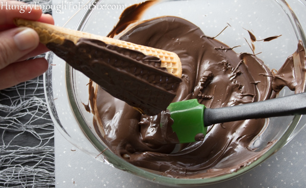 Sugar cone getting a layer of melted chocolate