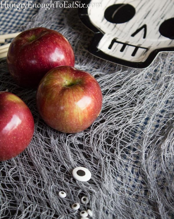 red apples on gray netting with a skull paper plate nearby