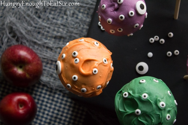Purple, orange and green coated apples with candy eyes