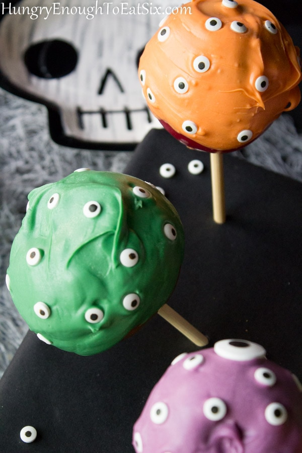 Black stand holding apples on sticks with candy coatings and eyeballs.
