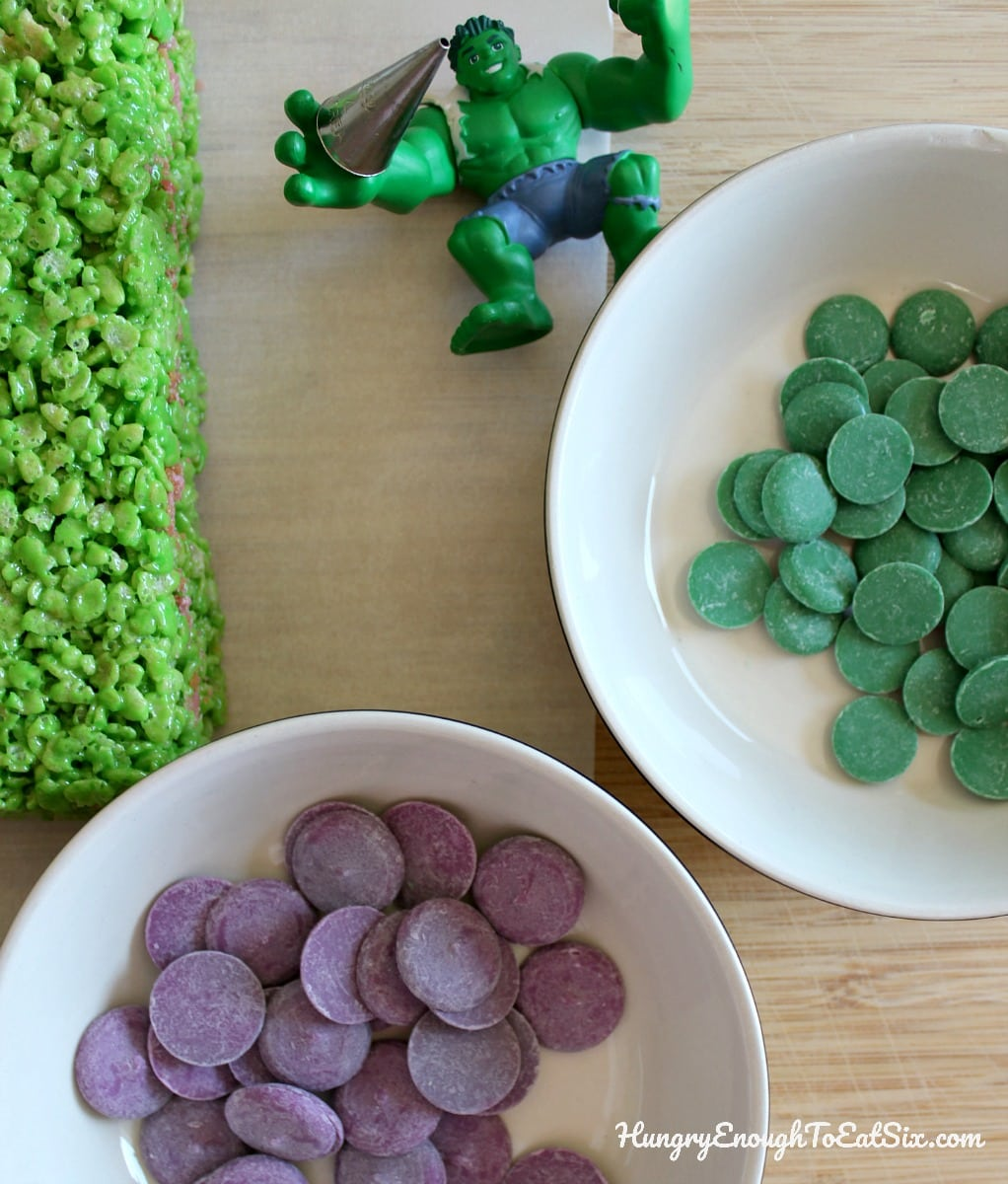 Green and purple candy melts in bowls next to a Hulk toy