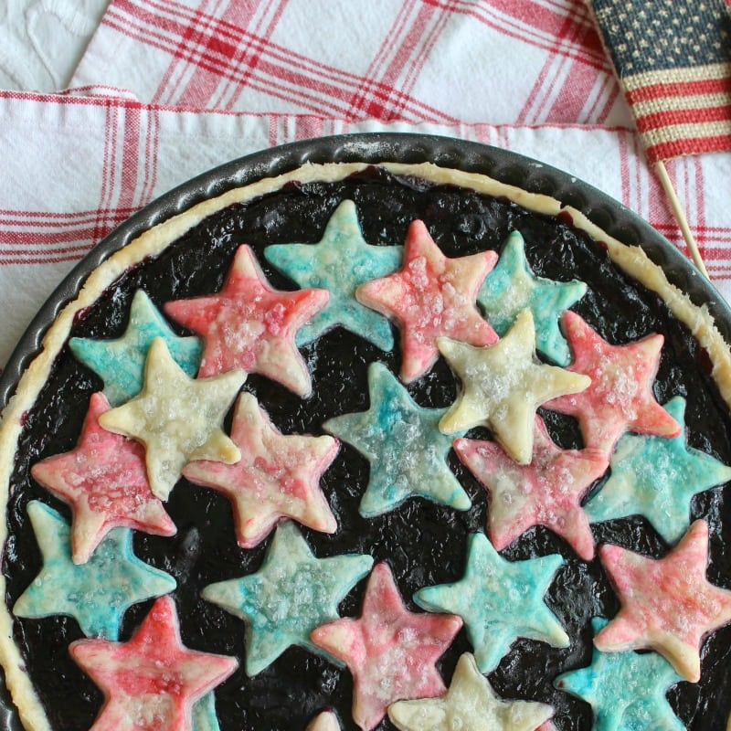 Cherries Blueberries + Stars Tart! A summery fruit tart with a sweet filling of cherries and blueberries! And atop the tart a few red, white and blue stars - for the 4th of July or anytime.