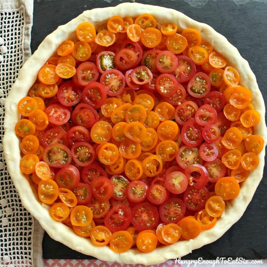 Cherry Tomato Basil Tart! The beautiful flavors of basil and sweet tomatoes come together in this cheesy tart!