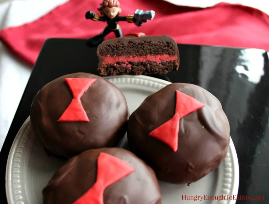 Chocolate covered sandwich cookies with red buttercream filling on a grey plate, with a Black Widow toy figure.