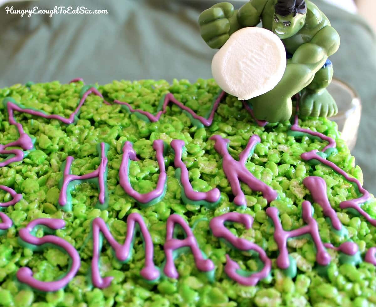 Green crispy marshmallow treats with purple and green writing, Hulk toy holding a marshmallow