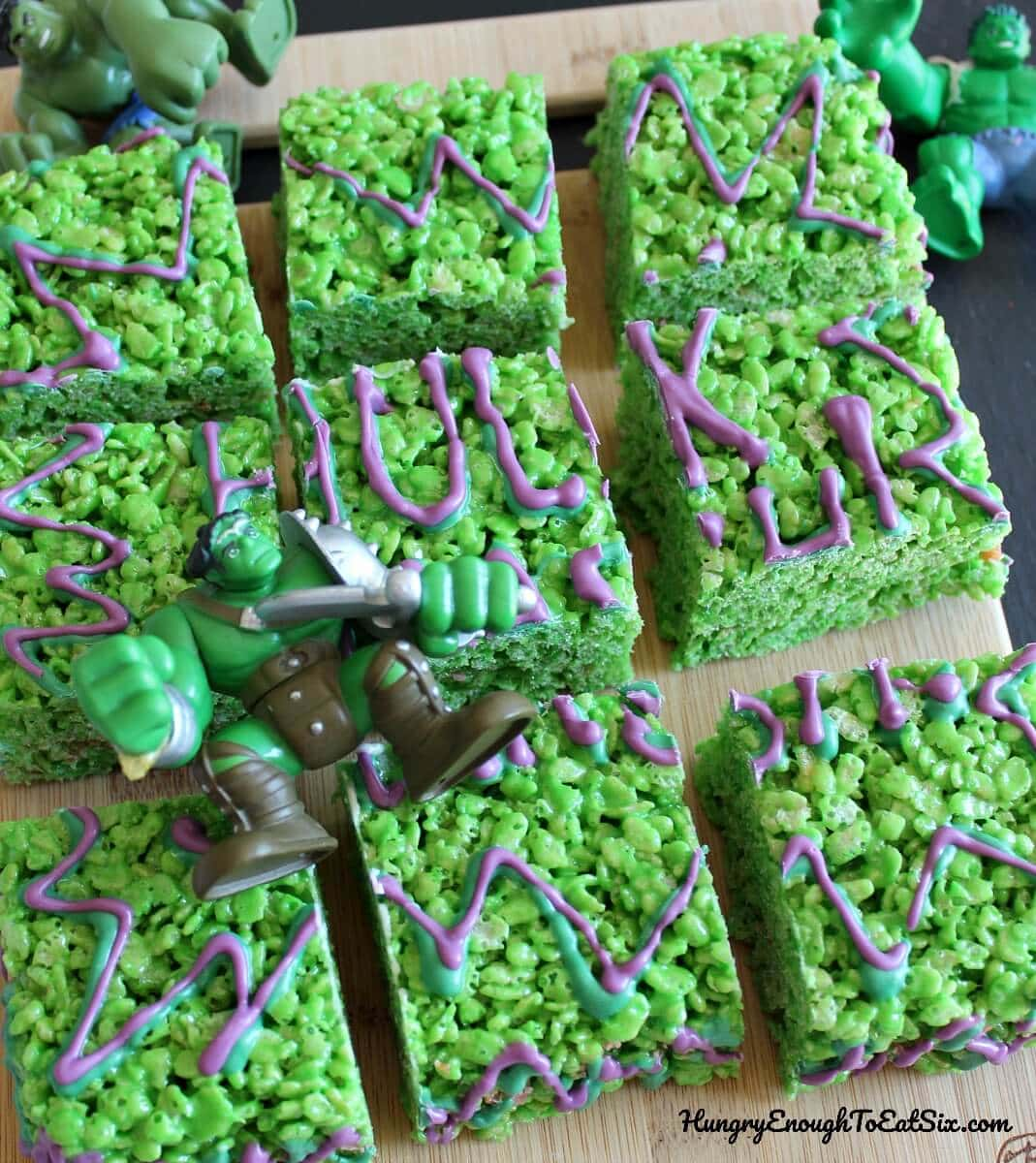 Green crispy marshmallow treats cut into 9 squares with Hulk toy laying on top