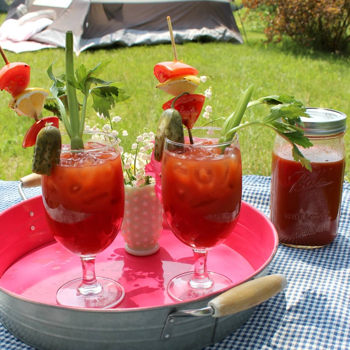 Garnished Bloody mary drinks on a metal tray