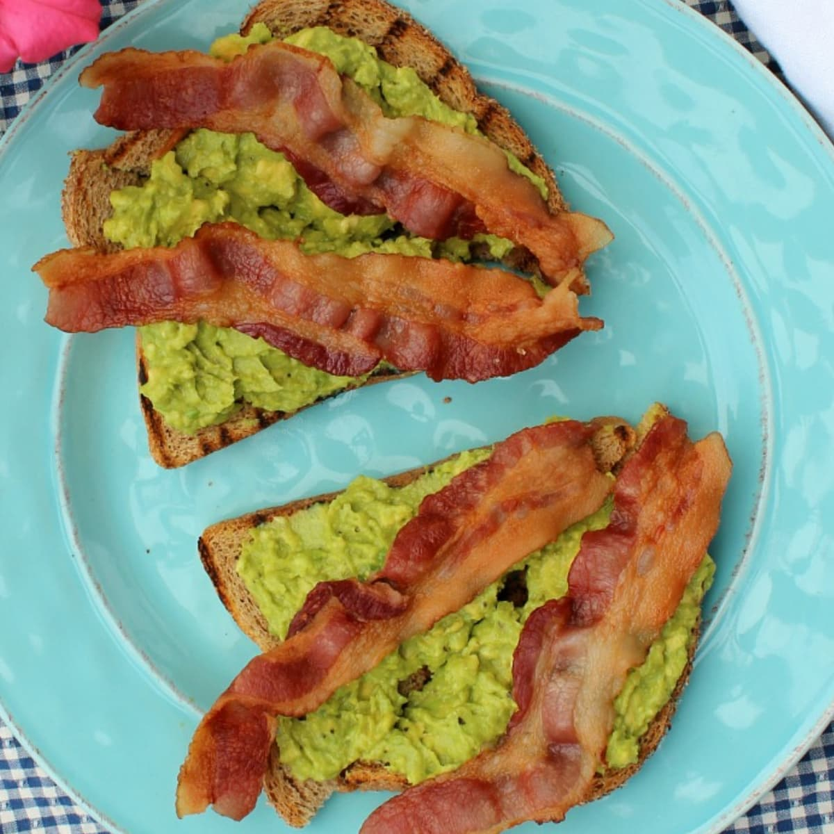Two slices of avocado toast with bacon on a plate