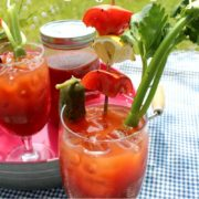 Bloody Marys on a pink tray with veggie garnishes.