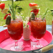 Pink tray with two glasses of Bloody Mary drinks.
